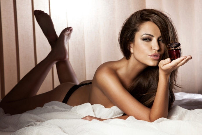 Photo of sexy brunette lady posing with perfume.