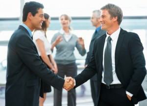 Businessmen shaking hands with colleagues in background